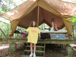 Katy wit her early bird t-shirt in front of her tent.
