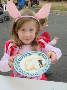 This little girl, her mom and brother were pigs and their dad was the big, bad wolf. She's showing off the cookie she decorated.